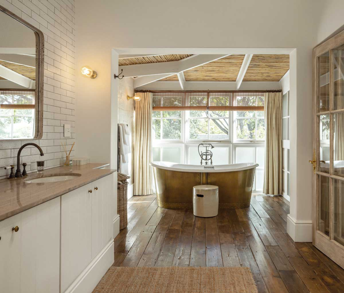Bateau bath in an aged brass skirt with Britannia bath mixer with levers in an aged brass finish ta Akademie Street Hotel by Victorian Bathrooms